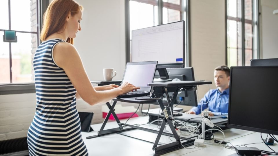woman working at standing desk with the wrong height