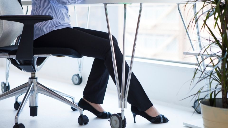 female office worker sitting at desk with her feet visable