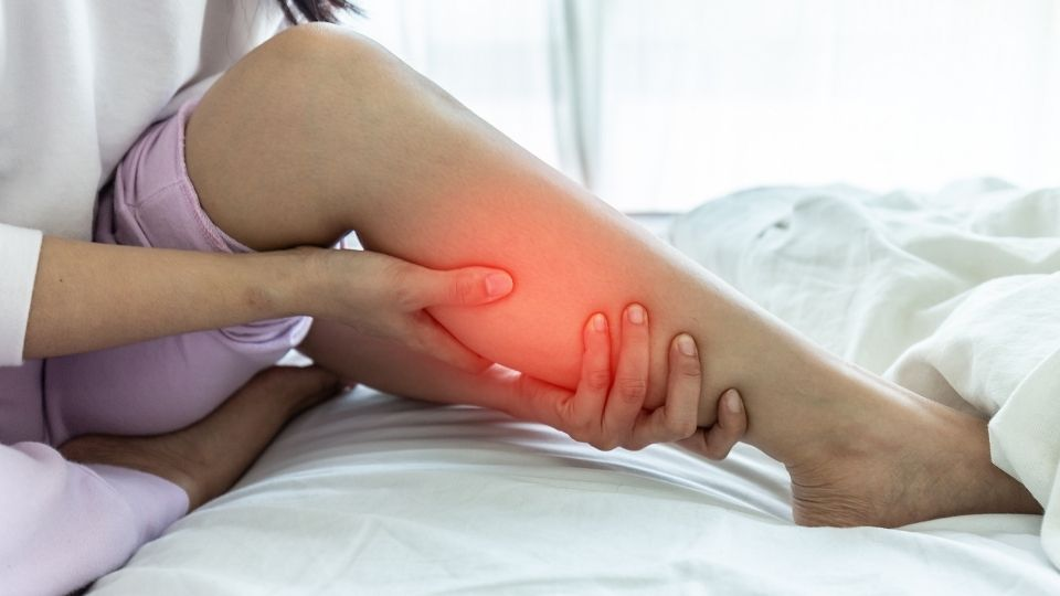 woman holding her calf in pain from poor blood circulation