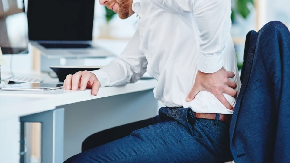 man experiencing back stiffness while working at a computer