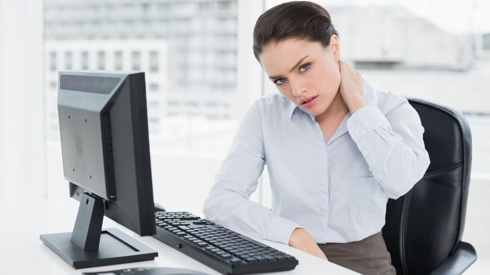 woman experiencing neck pain from improper monitor height