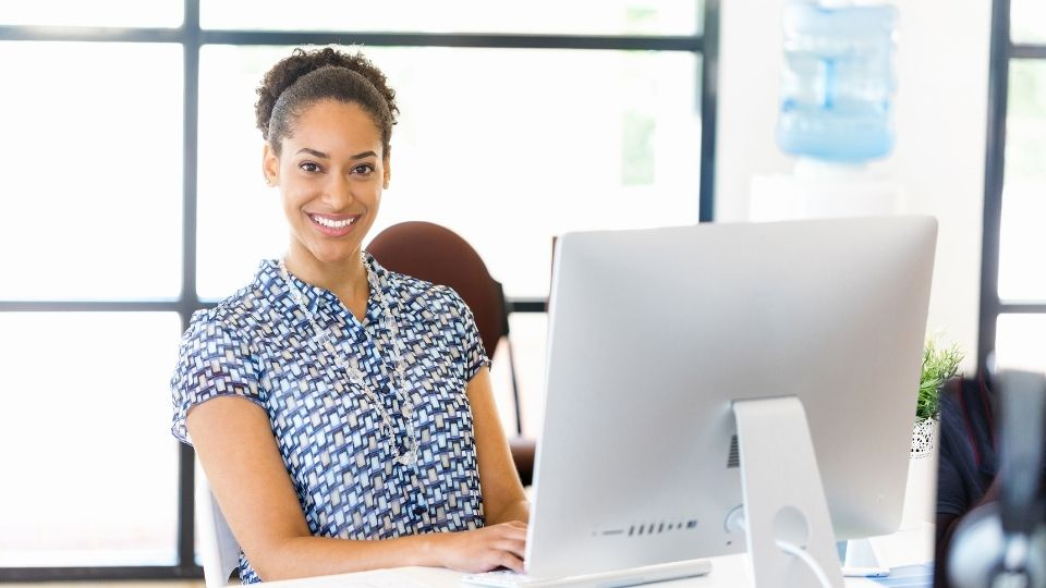 woman sitting at a desk in front of her computer