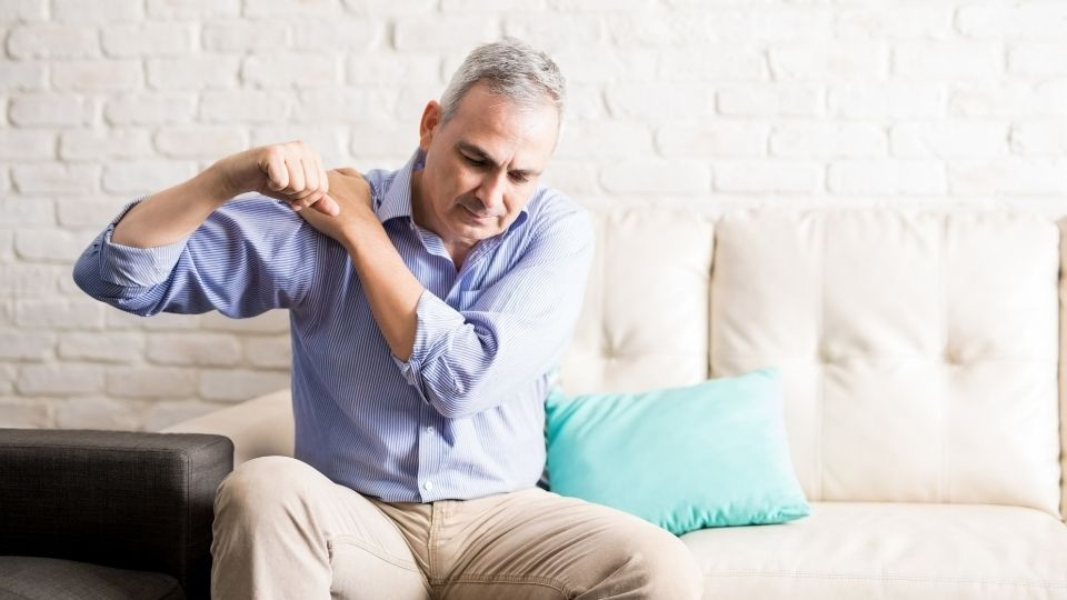 man sitting on couch experiencing shoulder pain