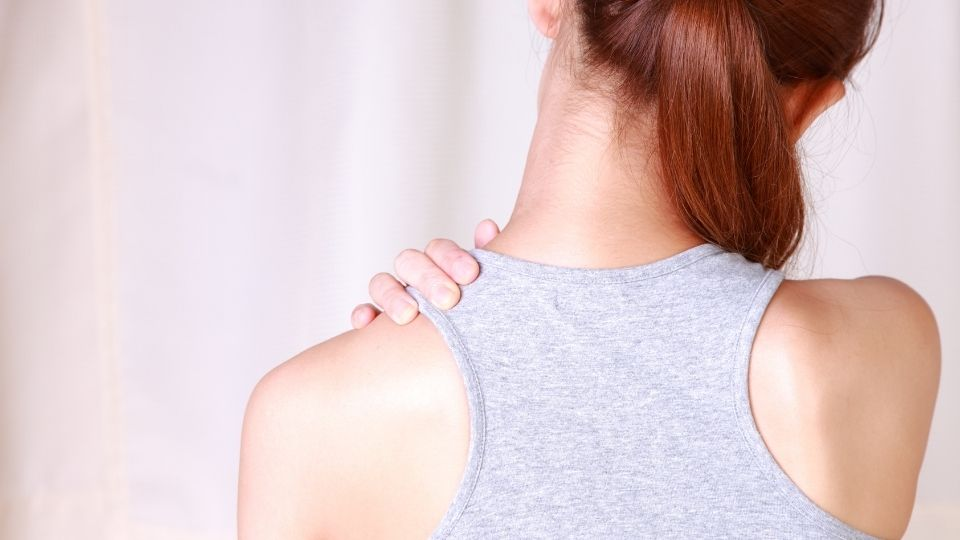woman holding upper back and shoulder from pain