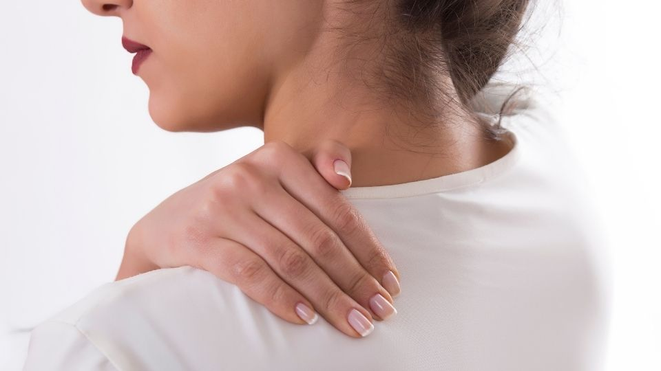 woman with her hand on her neck and shoulder