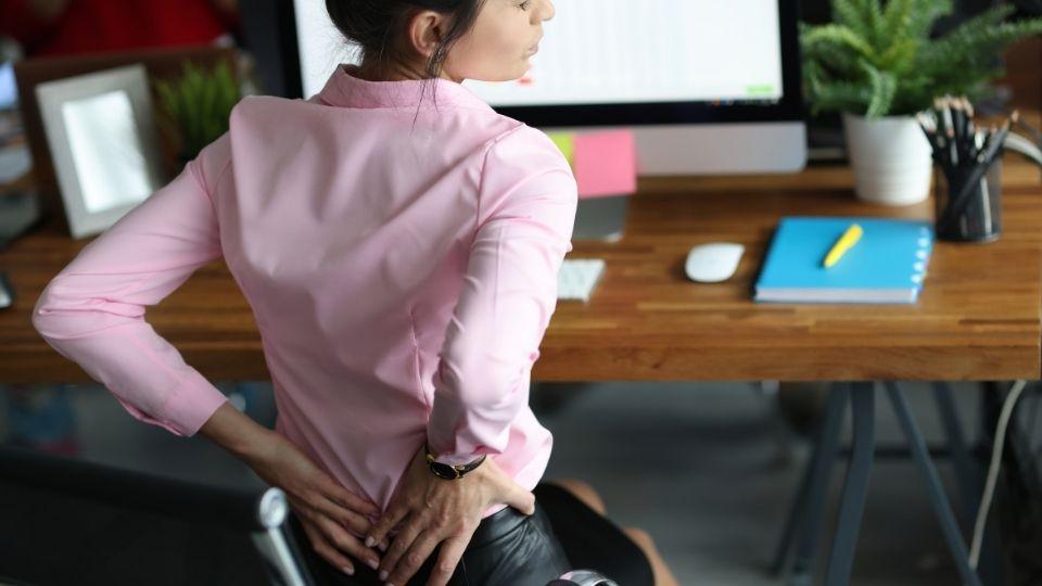 woman sitting office chair tailbone pain