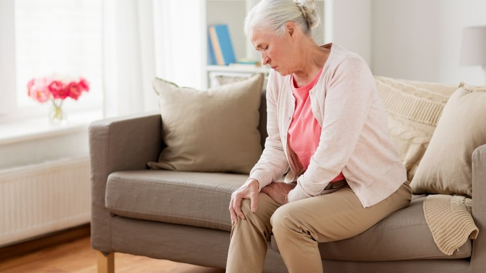 older woman sitting on a couch holding her knee