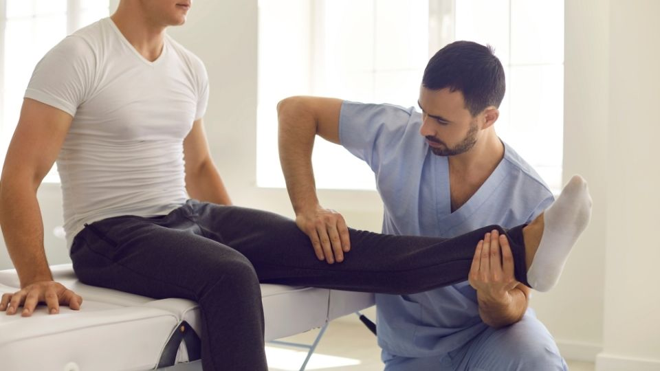 doctor treating patient with knee pain