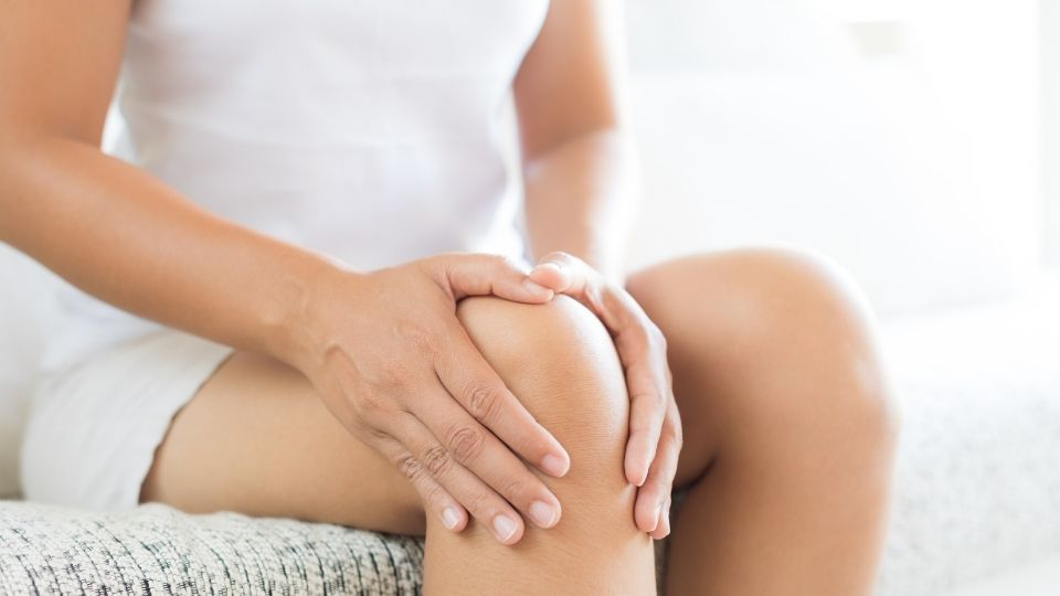 woman sitting with knee pain