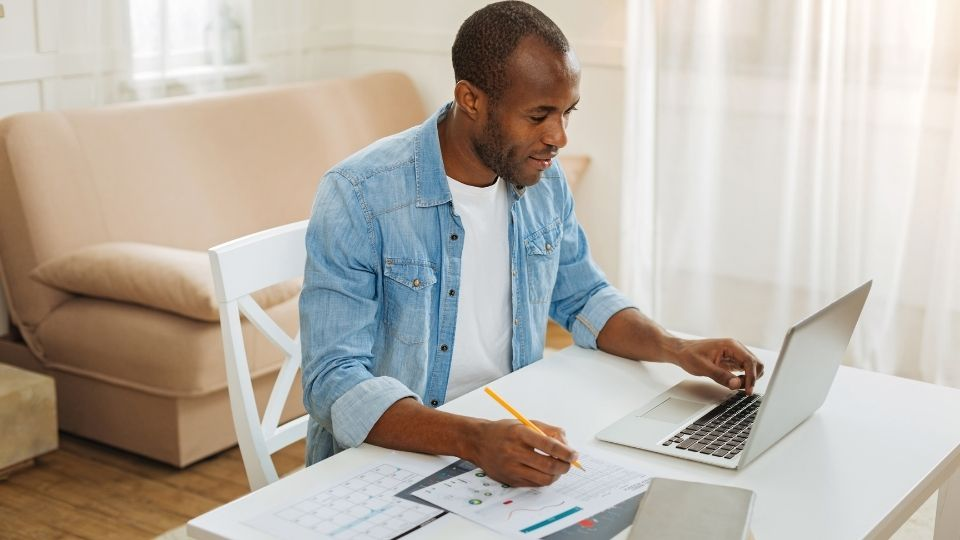 man working from home at his dining table