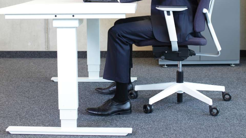 man sitting at desk with both legs and feet in the correct position to avoid weak legs while sitting
