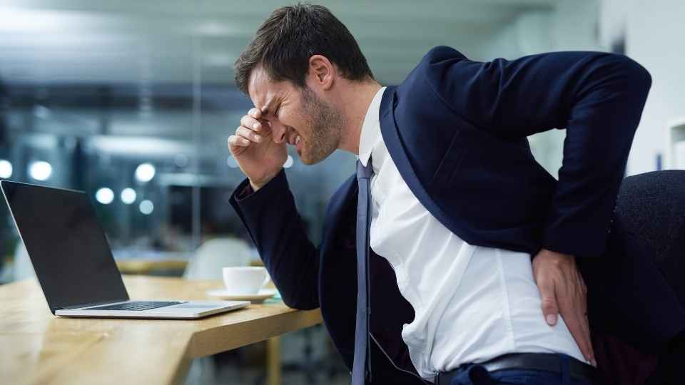 man sitting at desk with poor posture and back pain