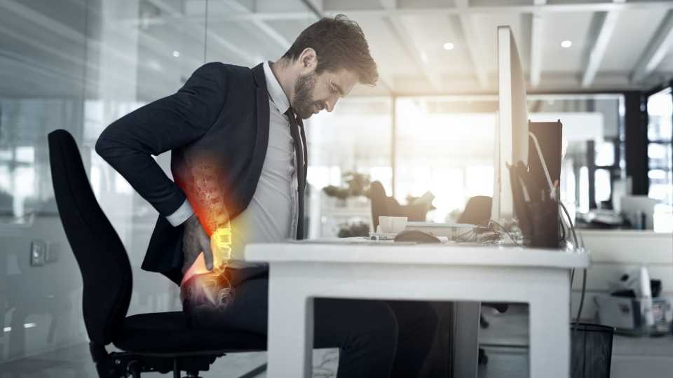 man sitting at a desk with poor posture and backpain