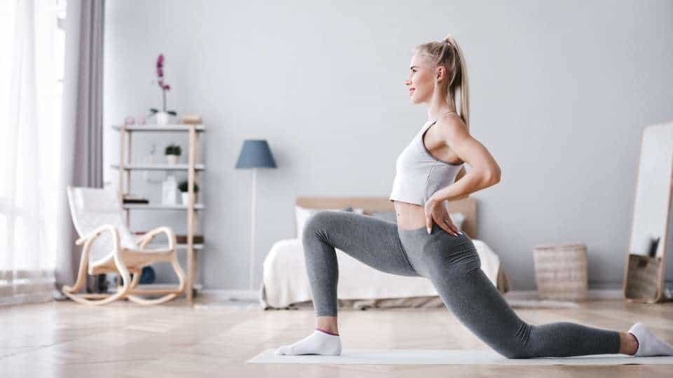 woman in her room stretching her legs muscles