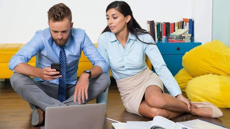 man and woman working while sitting on the floor